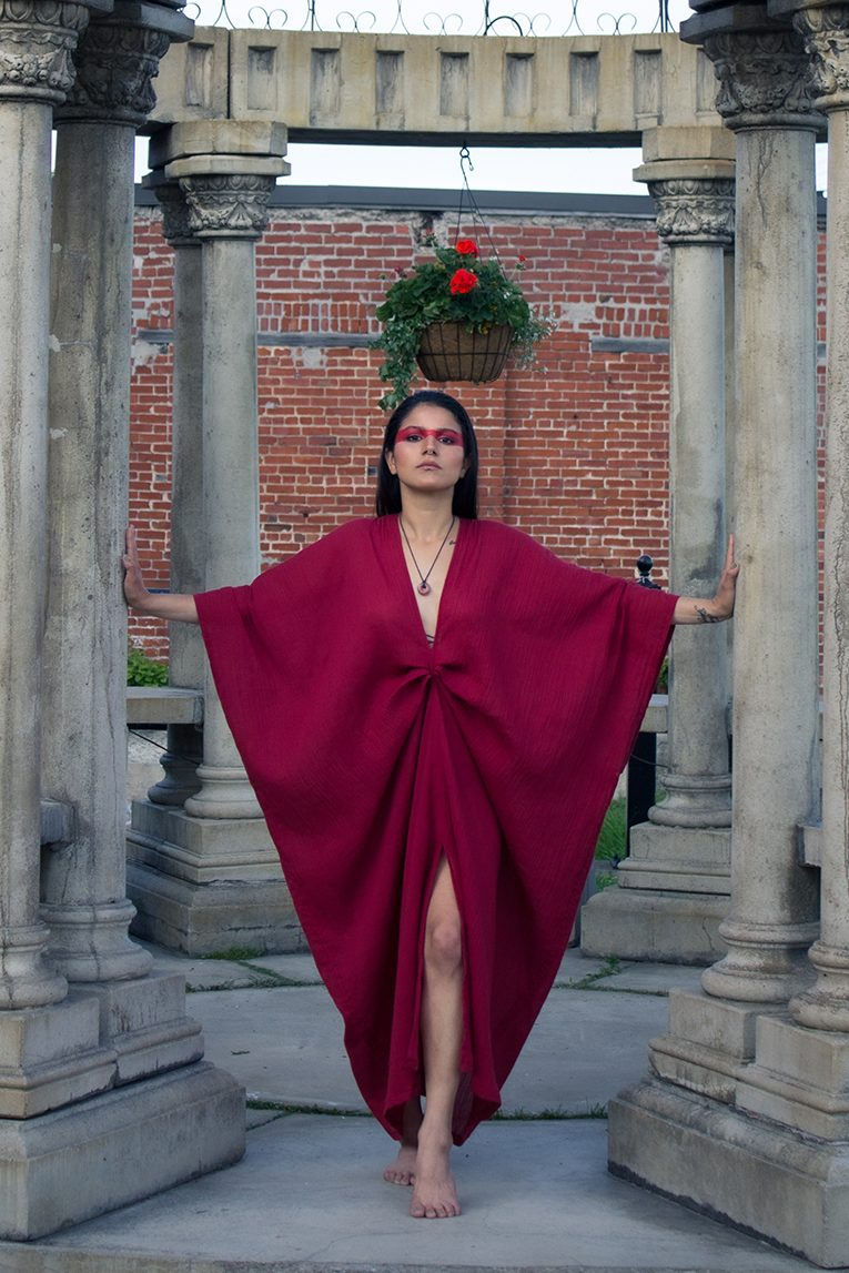 Woman in temple wearing a red organic dress