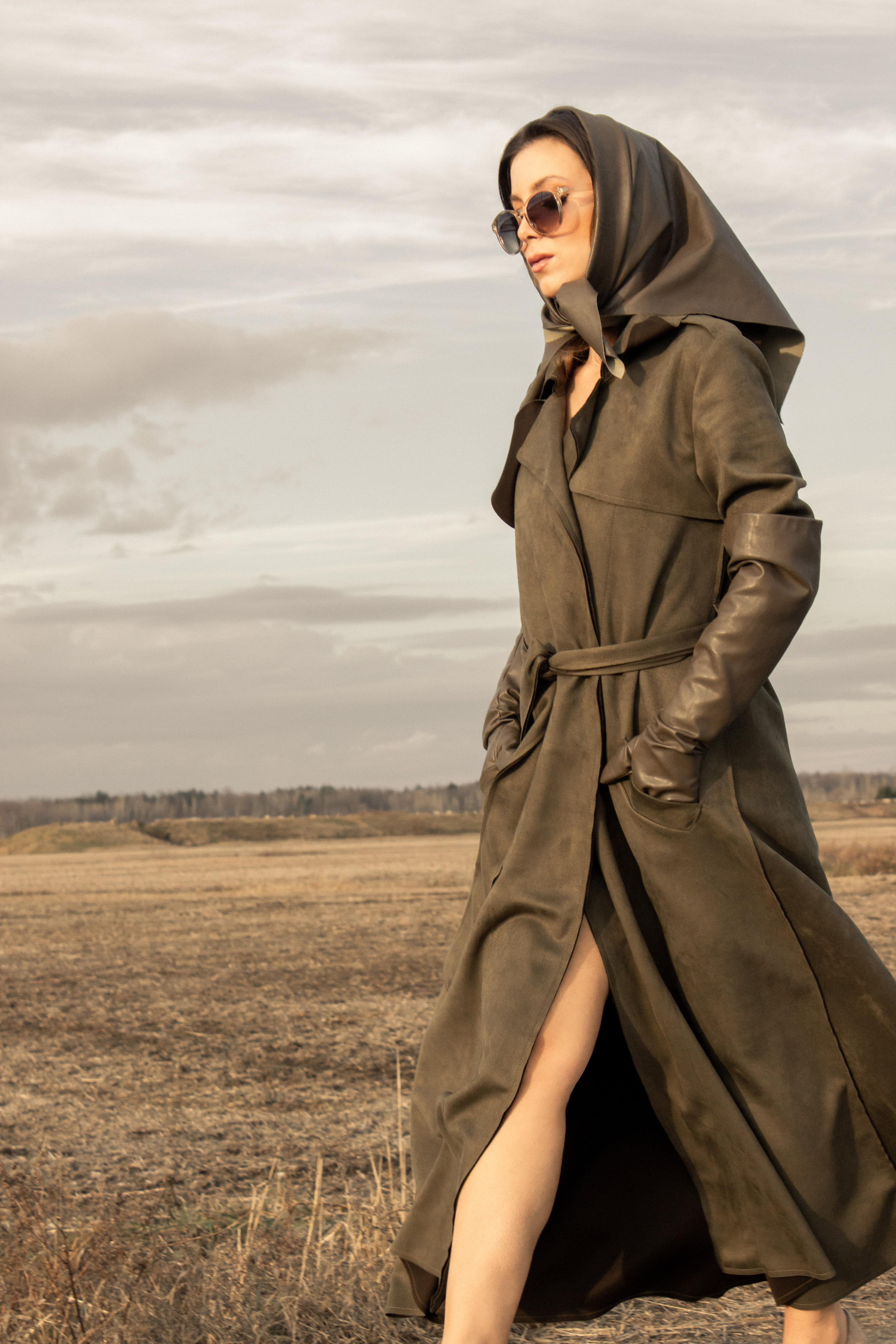 Woman wearing green vegan trench coat walking in the countryside