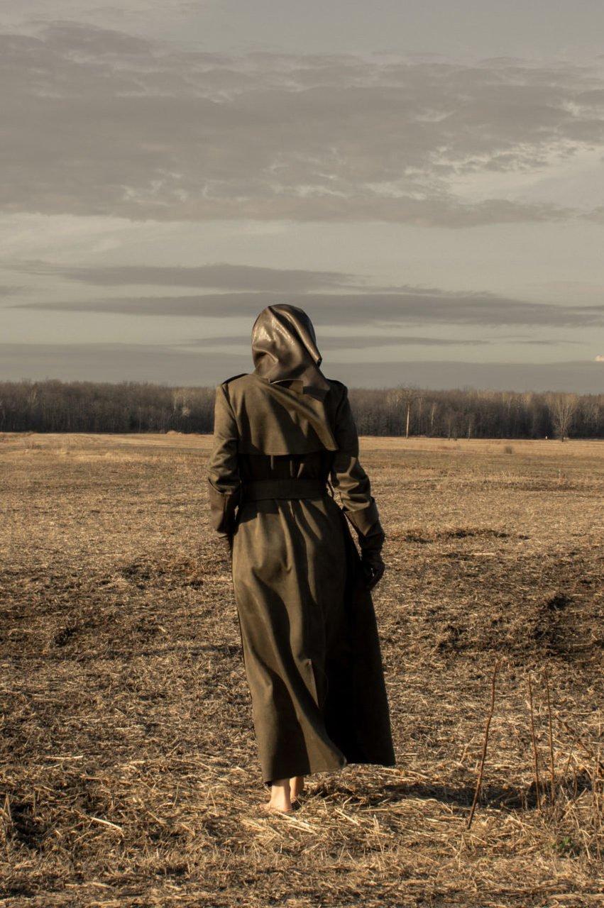 Woman wearing vegan green trench coat in countryside