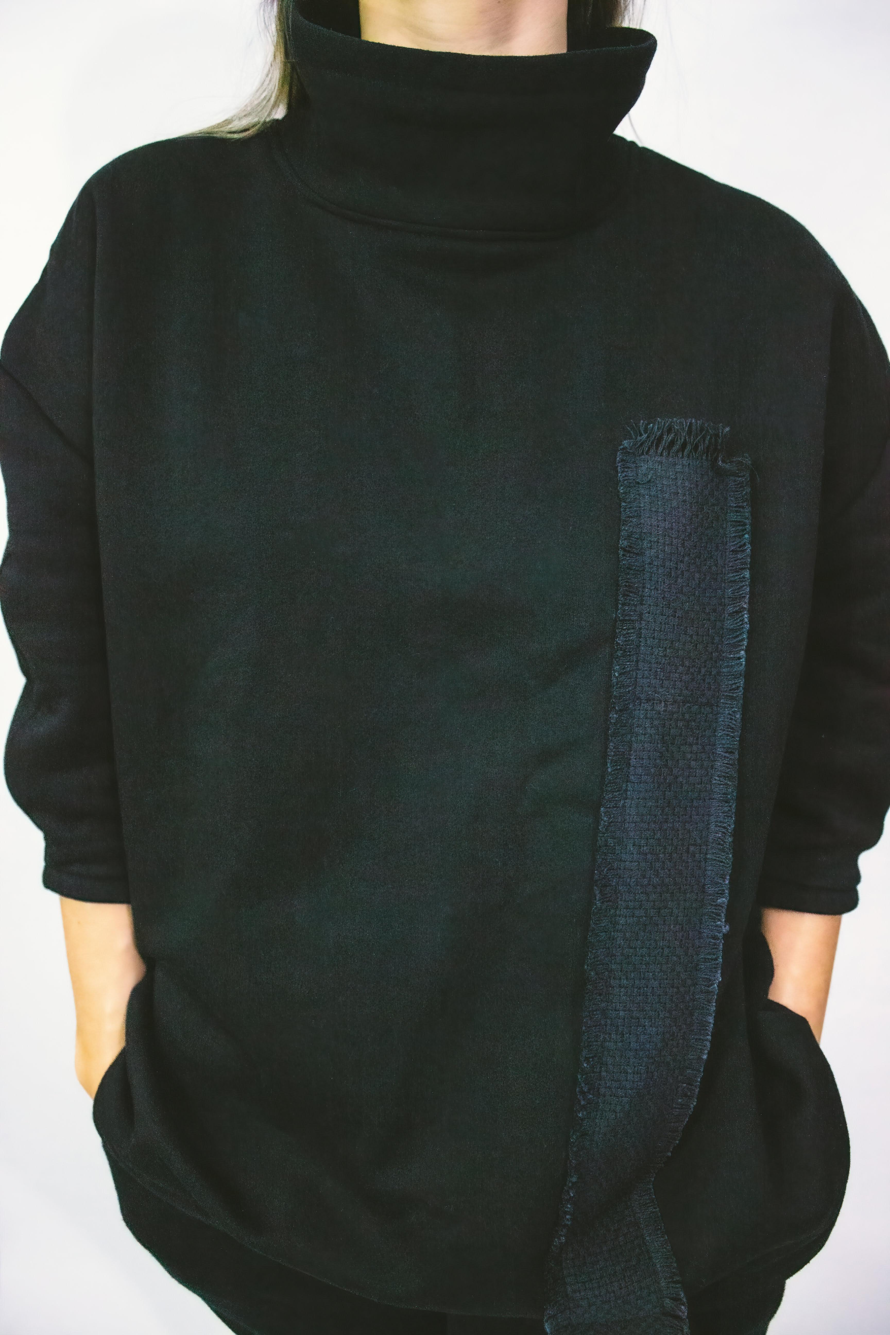 Woman wearing black high-collar sweatshirt