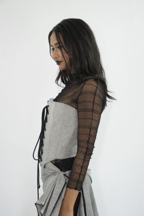 Woman wearing grey elizabethan cotton corset with gun metal eyelets tied at the front with black cotton cord