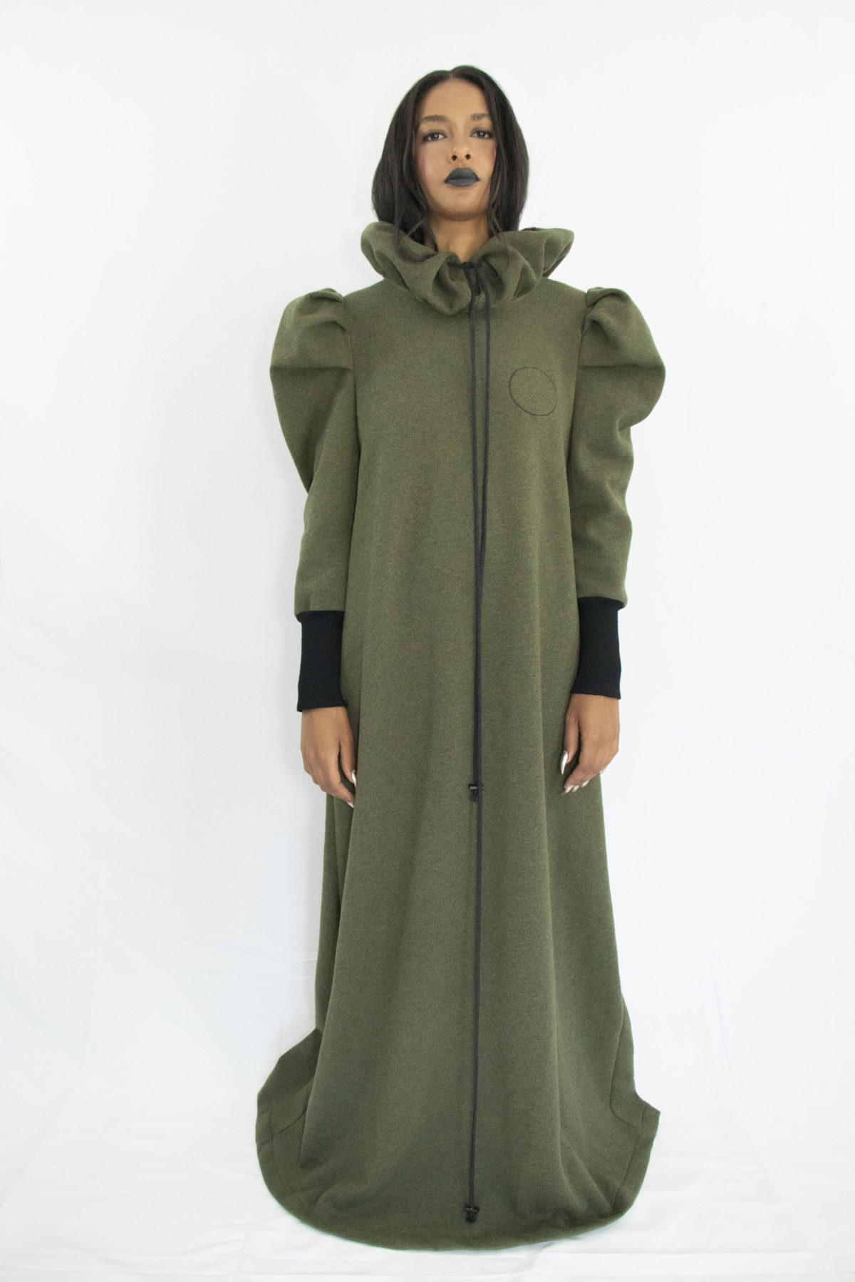 Woman wearing long forest green dress in organic cotton with gathered ruff collar and draw strings, puffy sleeves and long rib cuffs