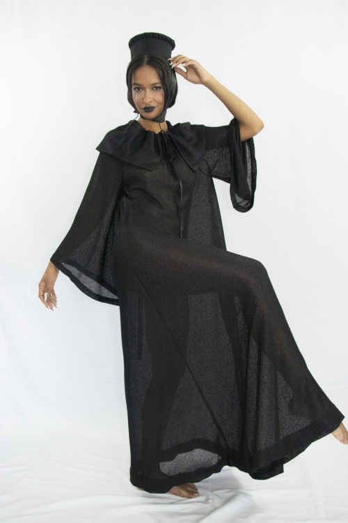 Woman wearing black sheer a-line dress with cape collar