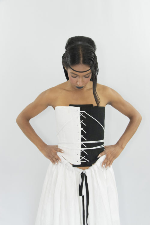 Woman wearing black & white cotton and linen zero waste contrasting front laced corset