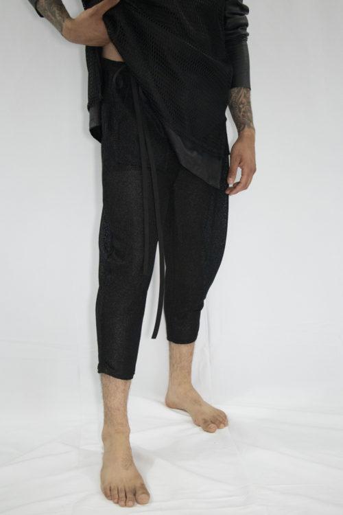 Man wearing three-quarter sheer mesh pants with front pocket