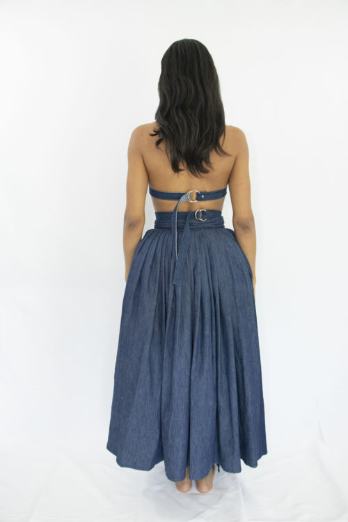 Woman wearing dark blue denim wrap assymetrical skirt with side pockets and oversized belt closure at the waist