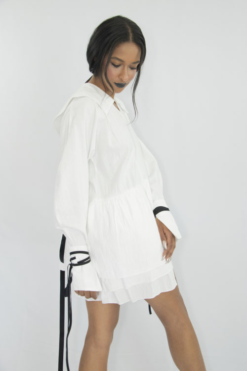 Woman wearing white organic cotton short dress with kimono sleeves, large cuffs with attachable contrasting black straps, pilgrim collar and gathered panels at the waist