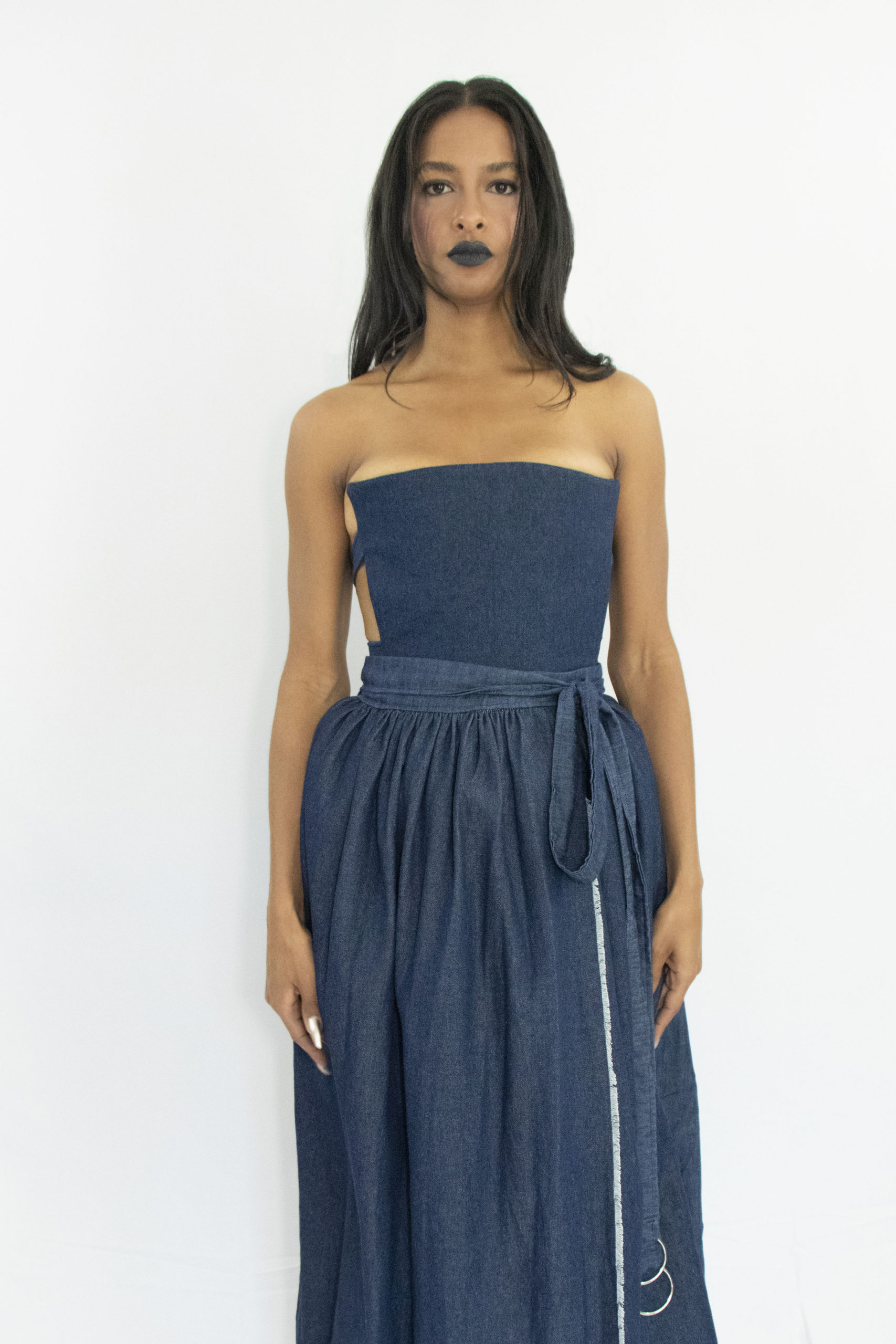 Woman wearing dark blue denim corset with straps buckled and tied at the back in zero waste cotton
