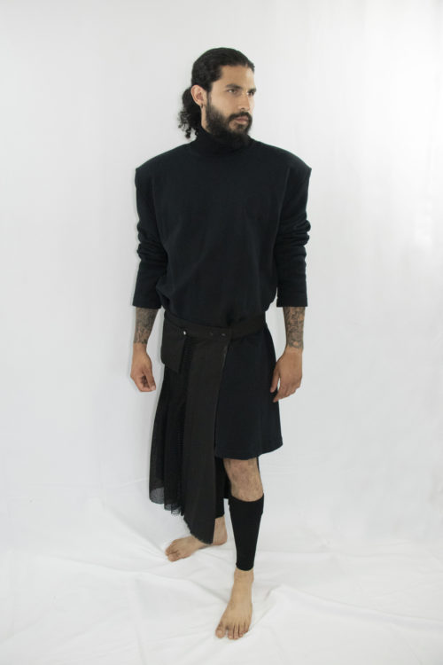 Man wearing black assymetric pleated kilt with front pocket and snap-belt made from zero waste and organic materials