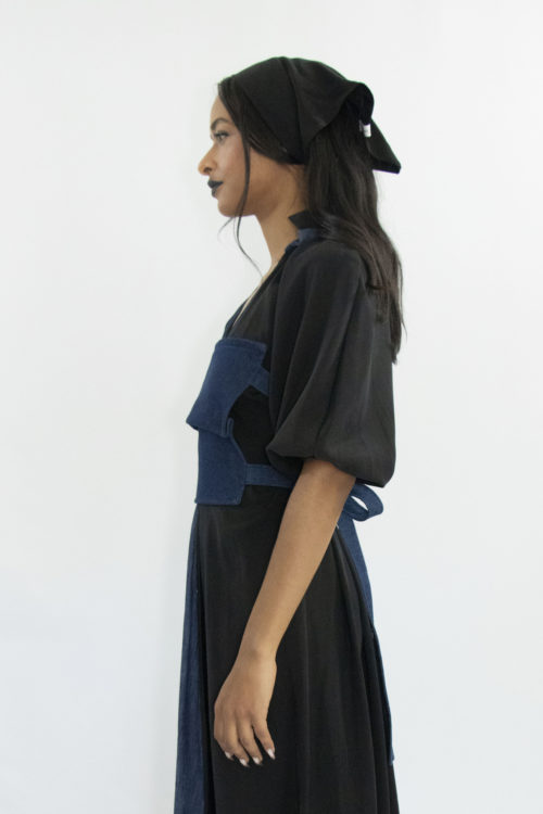 Woman wearing dark blue denim apron-style corset with belts closure at the back