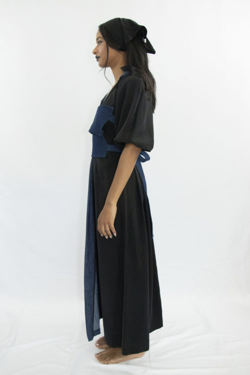 Woman wearing black and blue long a-line dress with ruff collar and gathered kimono sleeves made from organic hemp, cotton and sustainable lyocell