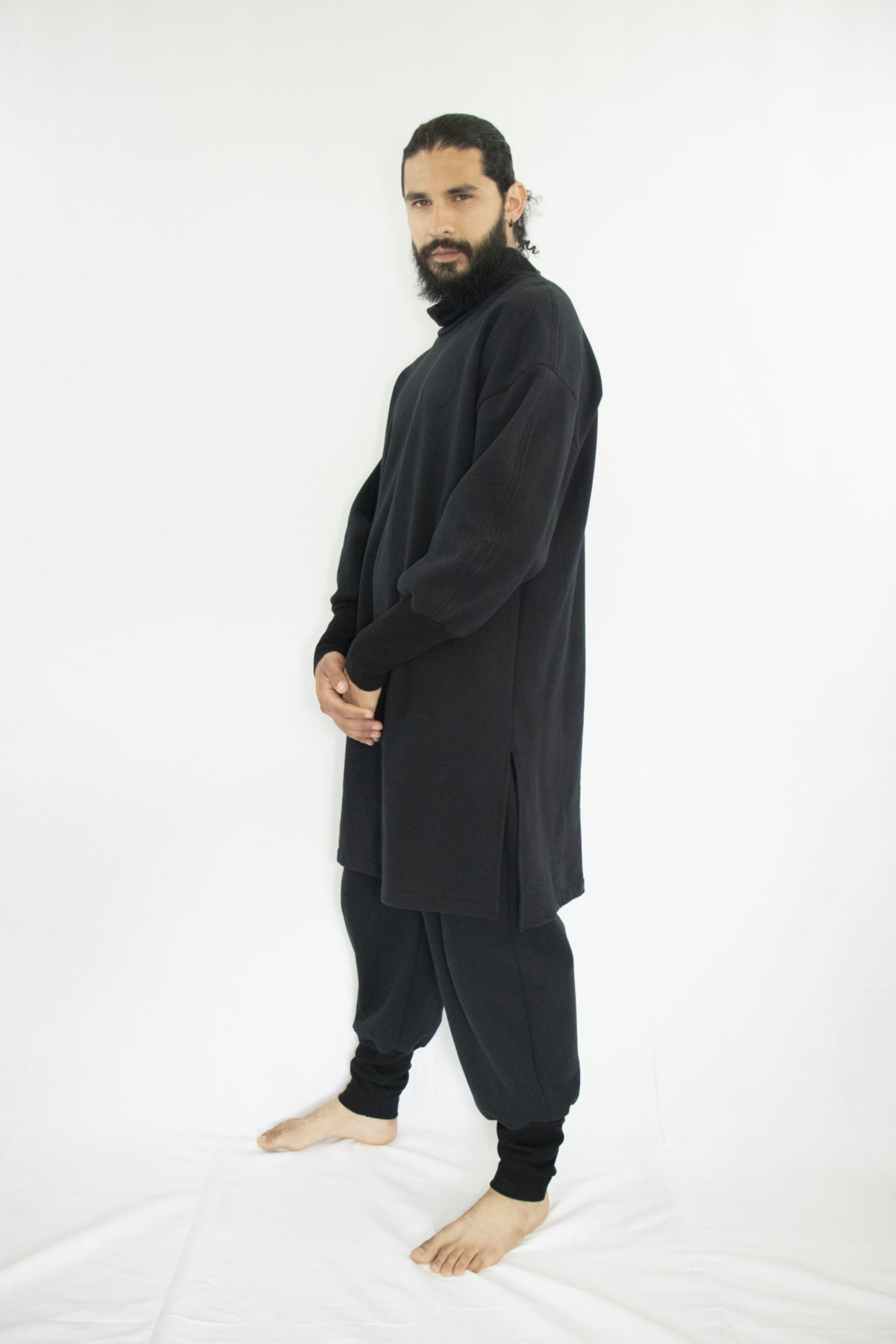 Man wearing organic black unisex tunic with long sleeves and high collar