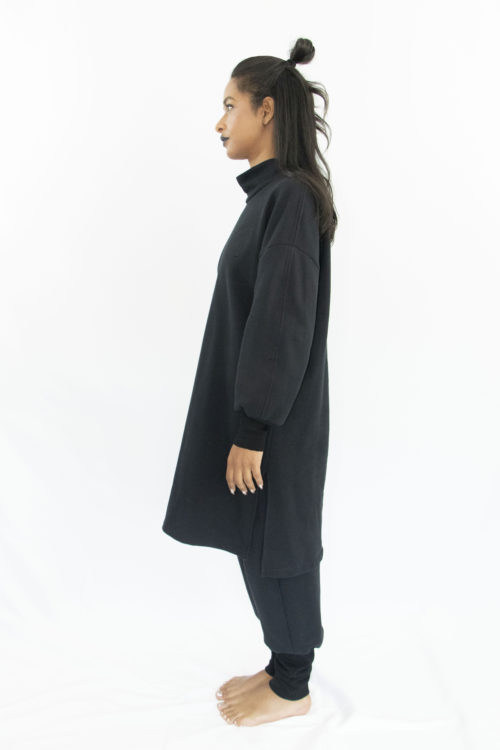 Woman wearing organic black unisex tunic with long sleeves and high collar