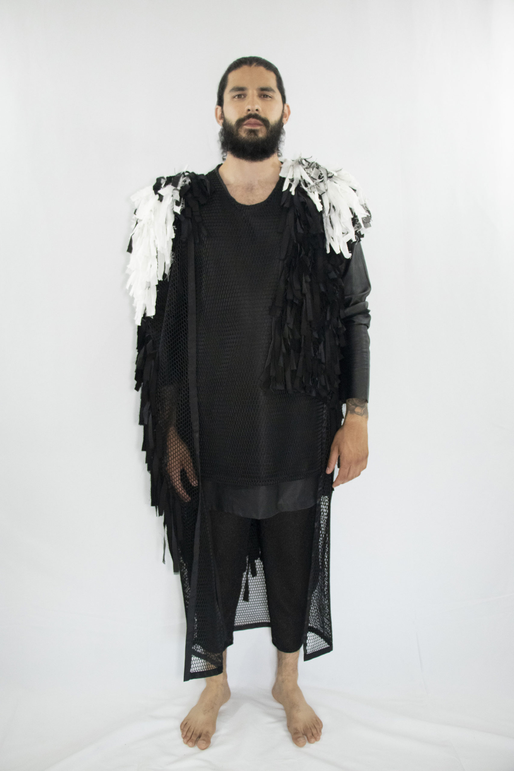Man wearing black unisex vest made out of cotton, linen and lyocell fringes fron zero waste materials